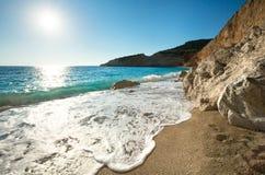 Porto Katsiki beach (Lefkada, Greece). Beautiful summer coast Porto Katsiki beach on Ionian Sea (Lefkada, Greece) with sun in sky and wave Royalty Free Stock Photo