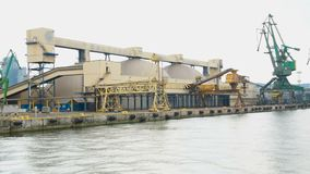 Porto marítimo com equipamento para a carga do armazenamento e da carga a bordo das embarcações filme