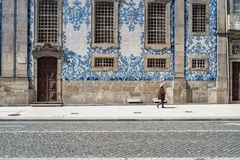 Porto, Portugal - April 4, 2017: Woman walking in front of a tiled facade of Igreja do Carmo in P royalty free stock photo