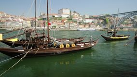 Porto rabelo boats. Porto, Portugal - August 13, 2017: Picturesque old Oporto waterfront with Ribeira skyline. A traditional rabelo boats on Douro River with Dom stock video footage