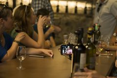 Porto, Portugal, August 21, 2018: port wine Tasting in cellars. At the table with bottles of port tourists sit. They`re holding. Wine glasses. Video is being stock image