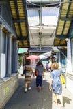 Porto, Portugal 12 augustus, 2017: De toeristen die door de geroepen marktdoorgang lopen doen Bolhao op de achtergrond zeer besch Royalty-vrije Stock Fotografie