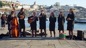 Porto, Portugal - circa October 2018:Young Students play classical portuguese music. Porto, Portugal - circa October 2018:Yound Students music band at the douro royalty free stock photography