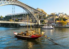 Porto/Portugal - 27 de novembro de 2010: Panorama da cidade, da ponte metálica de Dom Luis sobre o rio de Douro e do barco de Rab foto de stock royalty free