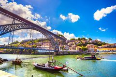 PORTO / PORTUGAL - JUNE 26, 2009: Traditional boats in Douro river and Dom Luis iron bridge royalty free stock photos