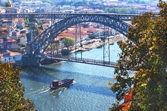 Porto, Portugal – May 2, 2019: Picturesque panoramic view of metal Luis I bridge, Douro river with boat and colorful old houses. Porto, Portugal royalty free stock photos