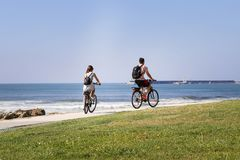 Couple young people riding a bike by the ocean royalty free stock images