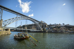 PORTO, PORTUGAL - Ribeira, traditional boats at Douro river in Old Town, Luiz iron bridge in background. Stock Photography