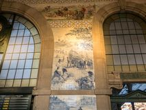 Porto, Portugal - Sao Bento train station interior with beautiful azulejos blue tiles on the wall depicting historic scenes stock image