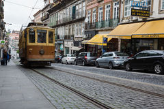 Porto, Portugal  street featuring an old brown and tan trolley on ancient cobblestones with a row modern cars Royalty Free Stock Images