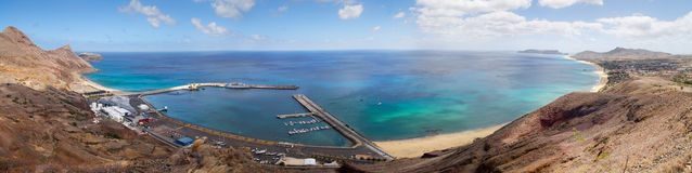 Porto Santo Harbour overview. Overview of Porto Santo bay, beach and harbour. Blue and green waters under a clouded blue sky. A ship is docked and Vila Baleira Stock Images