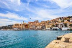 Porto Santo Stefano sjösida- och byhorisont. Argentario Tuscany, Italien Royaltyfri Bild