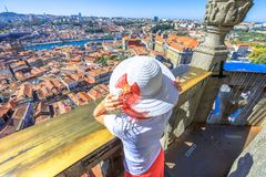 Porto skyline woman. Caucasian tourist woman looking Oporto skyline on Douro River and the colored buildings with tiled roofs from Clerigos Tower, symbols of Stock Photography