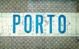 `-Porto ` som är skriftlig i blåttbokstäver över traditionell portugisisk gammal ` för tegelplatta`-azulejos i staden av Porto, P Royaltyfria Foton