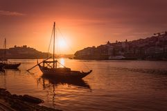 Porto at sunset: Duoro river with rabelo boat in front of setting sun and Arrabida bridge in background, Portugal stock image