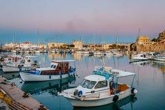 Porto velho de Heraklion com barcos de pesca e de porto durante o crepúsculo, Creta, Grécia fotografia de stock
