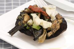 Portobello mushroom. A first course dish with a portobello mushroom topped with spring onions and blue cheese stock image
