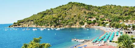 Portoferraio panoramic view, umbrellas, Elba Island. Portoferraio bay, panoramic view, umbrellas, landscape, reef, boats and coastline, romantic landscape and Royalty Free Stock Photography