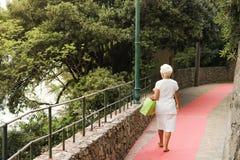 Portofino, Itália, o 19 de julho de 2017: Mulher idosa que anda afastado na rua imagens de stock royalty free