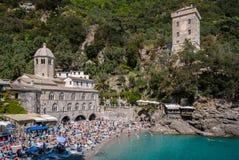 PORTOFINO ITALIEN - APRIL 30, 2017: Fullsatt strand framme av den San Fruttuoso abbotskloster under en solig eftermiddag Royaltyfri Bild