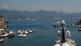 Portofino Italien - Juni 13, 2017: panoramautsikt från den Portofino hamnen med färgrika hus och fjärden med yachter i solig dag, arkivfilmer