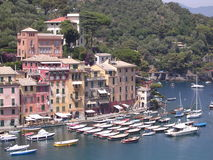 Portofino, Italy. The Wooded Italian hills fall into the blue Mediterranean. nestling in a cove are the bightly painted houses of the harbor of Portofino. Small stock image