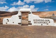 Portone bianco dell'arco del segno tipico del comune vicino al villaggio di Betancuria con il paesaggio nei precedenti, Fuerteven Immagine Stock Libera da Diritti