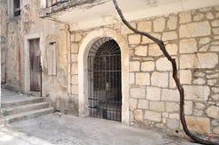 Portone del ferro in parete di pietra antica Fotografie Stock