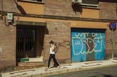 Portone del garage su una facciata di costruzione e donna con il telefono cellulare a Caceres fotografia stock