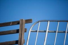 Portone di legno del metallo e del recinto giustapposto contro cielo blu immagine stock libera da diritti
