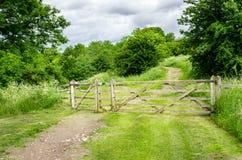 Portone di legno lungo un percorso attraverso la campagna Fotografie Stock Libere da Diritti