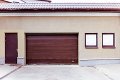 Portone ondulato marrone chiuso del garage del metallo con la entrata e il windo Immagini Stock Libere da Diritti