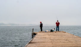 Portoroz, Slovenia - October 17, 2015: Local fishermen are fishing from a pier. In the hands of these rods. Stock Photos