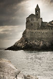 Portovenere church in a stormy day. Portovenere church, San Pietro, facing the sea with a coming storm. The photo has been taken from Palmaria island, in front Stock Image