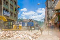 Portoviejo Ecuador - April, 18, 2016: Plockningspillror för tungt maskineri från förstörda byggnader efter tragiskt och arkivfoto