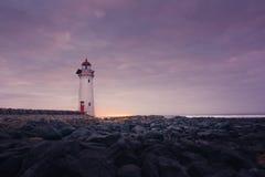 Portowa czarodziejska latarnia morska przy wschodem słońca z skałami Obrazy Stock