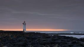 Portowa czarodziejska latarnia morska przy wschodem słońca z skałami Zdjęcie Royalty Free