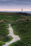 Portowa czarodziejska latarnia morska przy wschodem słońca z skałami i ścieżką prowadzi w kierunku Zdjęcia Royalty Free