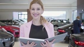 Porträt der angenehmen Frau in der rosa Jacke gehend in Richtung zur Kamera, die großen Buchabschluß hochhält Fahrzeuge sind in stock footage