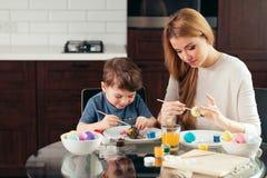 Porträt der glücklichen jungen Frau, die Ostereier mit ihrem entzückenden kleinen Sohn malt lizenzfreies stockfoto
