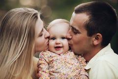 Porträt der reizenden jungen Familie, die zusammen draußen sitzt lizenzfreie stockbilder