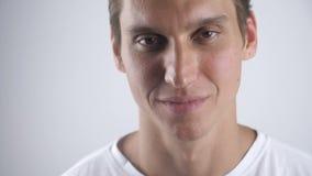 Porträt des gelächelten schönen Mannes, der zur Kamera auf dem weißen Wandhintergrund lächelt und schaut Abschluss oben innen stock video