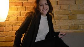 Porträt des jungen kaukasischen Mädchens mit dem gewellten Haar, das auf Sofa sitzt und mit großer Begeisterung auf angenehmem Ha stock video footage
