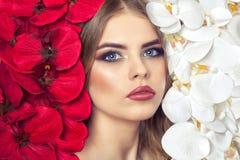 Porträt einer Frau mit schönem Make-up hält eine weiße und rote Orchidee in seinen Händen lizenzfreies stockfoto