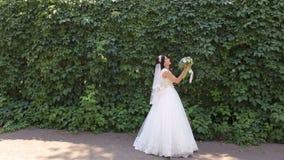 Porträt einer glücklichen Braut mit einem Blumenstrauß von Blumen geht in den Park stock footage