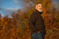 Porträt eines älteren Mannes draußen, gehend in einen Park lizenzfreie stockbilder