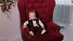 Porträt eines kleinen einjährigen Jungen in einem Smoking in einem Stuhl stock footage