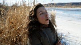 Porträt eines schönen Mädchens auf der Bank von einem gefrorenen Fluss Natur genießend, lachend und mit gelbem Stock spielend stock video