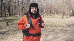 Porträt eines Touristen mit einem großen touristischen Rucksack, tragenden Gläsern, einem Winterhut und einer hellen roten Jacke  stock video footage