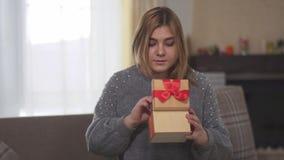 Porträt glückliches frohes bbw öffnenden Geschenks, das auf Sofa im Raum sitzt stock video footage